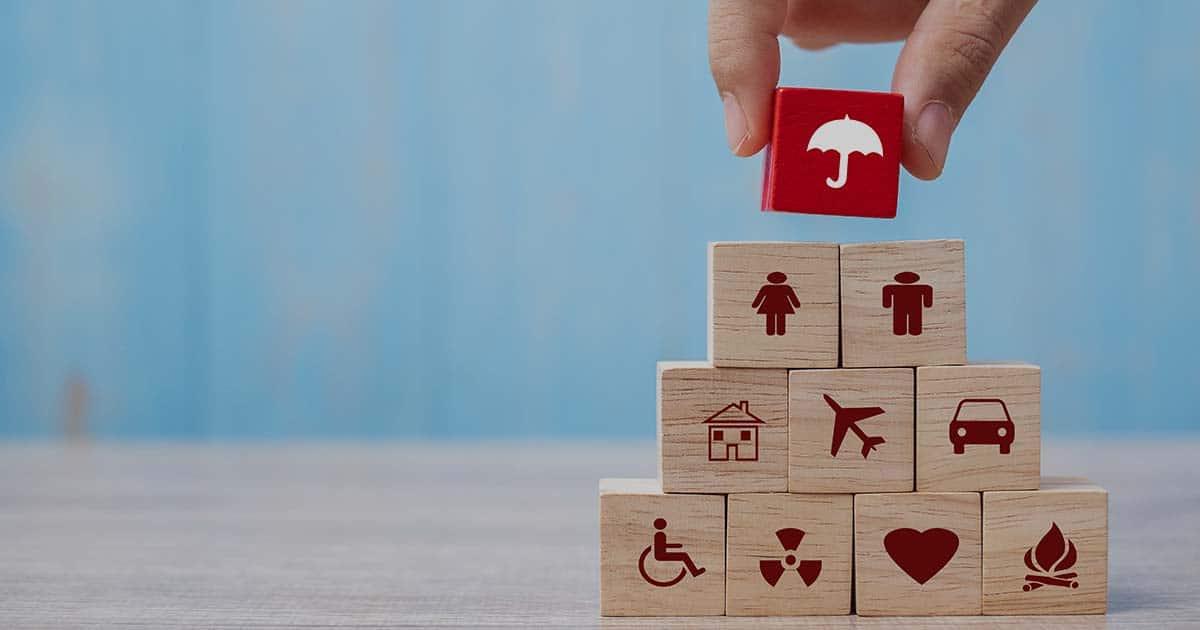 ACCES21 Fonds de dotation pour chef d'entreprise. Illustration de cubes en bois formant une pyramide. Les cubes ont des icônes. Une main pose le dernier cube rouge avec l'icône d'un parapluie