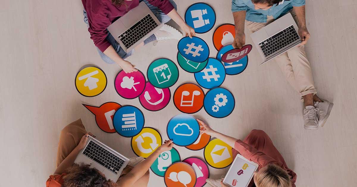 ACCES21 Fonds de dotation photo de trois personnes assises par terre avec des ordinateurs et tenant des feuilles en forme d'icône web
